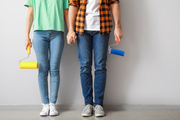 Young couple with paint rollers near light wall in new apartment