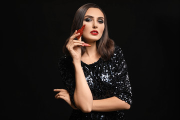 Wall Mural - Beautiful young woman with lipsticks against dark background