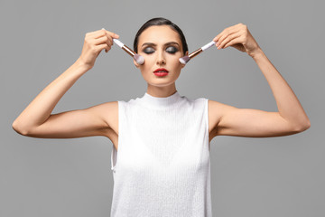 Wall Mural - Beautiful young woman with makeup brushes on grey background