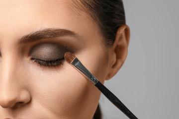Wall Mural - Beautiful young woman applying makeup against grey background, closeup
