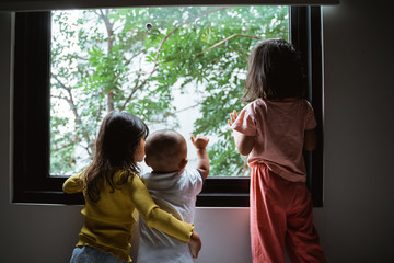 three asian little child seeing out of the window glass when standing in the bedroom Fototapete