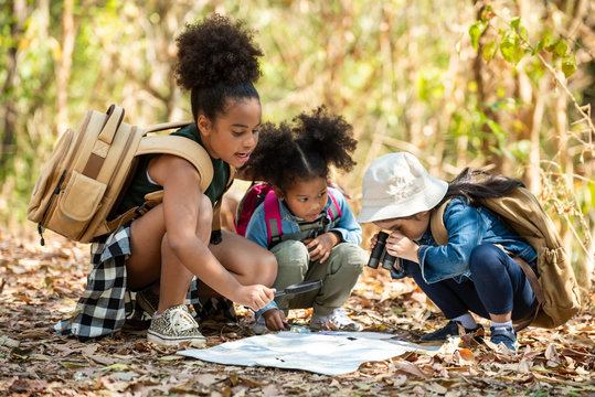 Group of happy pretty little girl hiking together with backpacks and sitting on forest dirt road with looking at the map for exploring the forest. Three kids having fun adventuring in sunny summer day