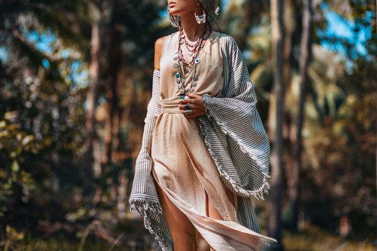 beautiful young stylish woamn in boho dress walking on a field at sunset