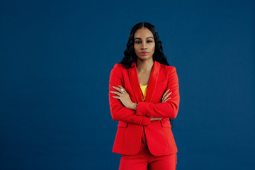 Portrait of a serious young woman entrepreneur in red business jacket with arms crossed isolated on blue