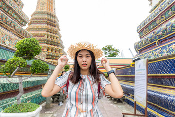 Fototapete - Beautiful asian tourist backpack women walking travel in buddhistm temple pagoda statue