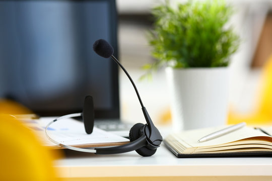 Empty remote office workplace with laptop pc and headset closeup. Receptionist or secretary of contact data center desktop keyboard device desk table ip telephony or callcenter voice message system