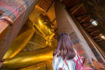 Wall Mural - Asian cute women travel in golden reclining buddha statue indoor temple pagoda