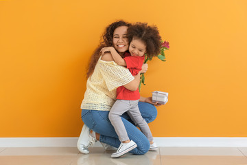 Little African-American girl greeting her mother near color wall