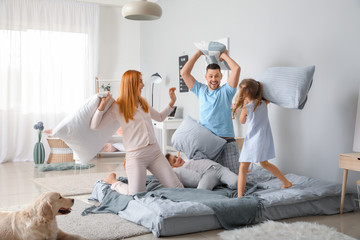 Happy family fighting on pillows in bedroom at home