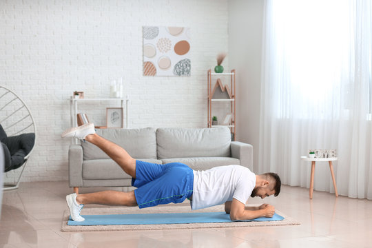 Sporty young man training at home
