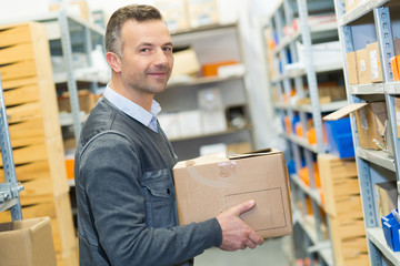portrait of man in storeroom holding cardboard carton
