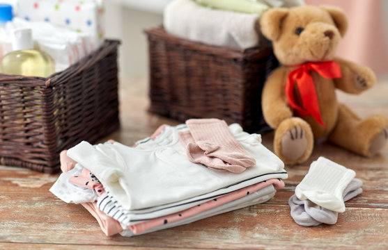 babyhood and clothing concept - baby clothes, teddy bear toy and baskets on wooden table at home