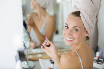 woman by mirror holding lipstick Wall mural
