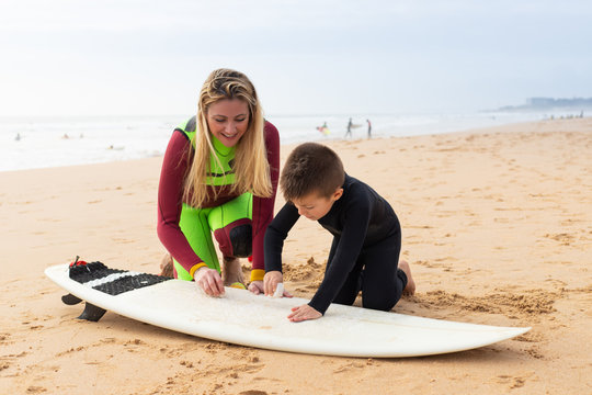 Mother and son waxing surfboard on sea coast. Cheerful mother and little son in wetsuits sitting on sand and waxing surfboard at ocean beach. Surfing concept
