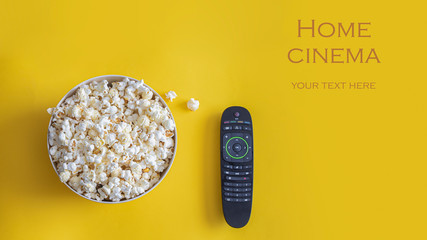 Popcorn bowl and remote control on yellow background.  Smart tv and home cinema concept.