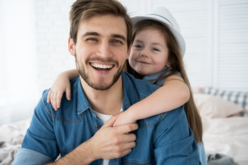 Portrait of handsome father and his cute daughter hugging, looking at camera and smiling while...