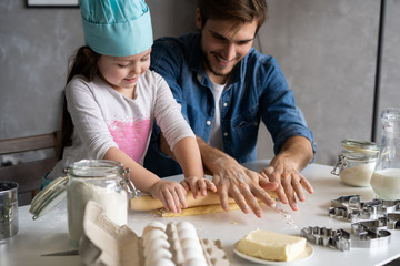Father and little daughter baking pastries. Family having fun in kitchen and getting ready for a party. Fototapete