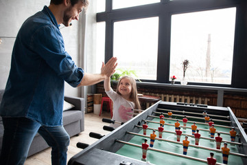 father and daughter playing table football at home