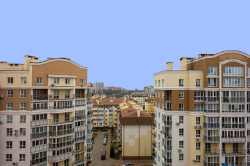 Modern urban architecture cityscape view under blue sky at daytime. Building roofs and facades in brown colors. Mortgage to buy private apartment concept