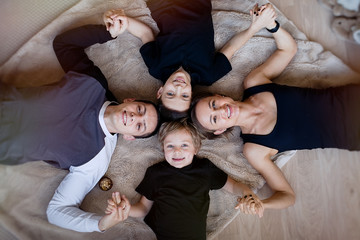 Happy family looking at camera and smiling while lying on the floor at home. Top view