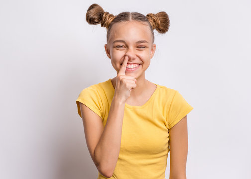 Portrait of teen girl pick her nose on grey background. Funny cute child with finger in nose. Health care and hygiene concept. Girl picking nose and laughs.