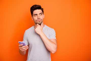 Photo of minded serious millennial guy hold telephone deep think new instagram blog post text arm on chin look side wear striped t-shirt isolated bright orange color background