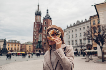 Tourist woman holding bagel obwarzanek traditional polish cuisine snack on Market square in Krakow. Travel Europe