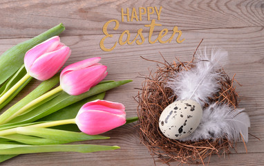 Easter nest and pink tulips on wooden background. Text Happy Easter.