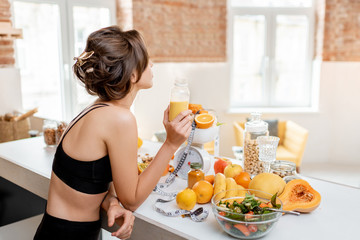 Poster de jardin Jus, Sirop Portrait of an athletic woman having a break, drinking juice while standing with lots of healthy fresh food on the kitchen. Concept of losing weight, sports and healthy eating