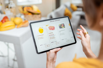 Woman shopping food online using a digital tablet at the kitchen, close-up view on a tablet screen....