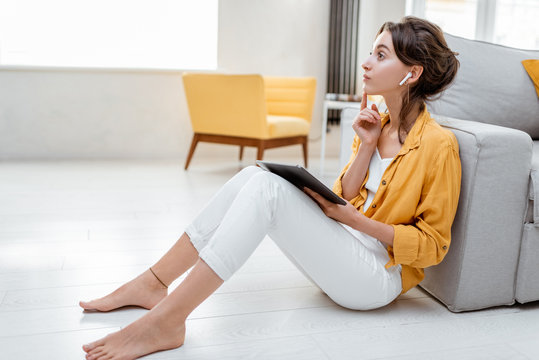 Young and cheerful woman working on digital tablet while sitting relaxed on the floor at home. Concept of leisure, freelance and mobile work