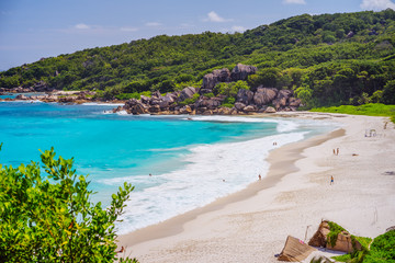 Grand Anse beach at La Digue island in Seychelles. Long white sand beach with blue lagoon, ocean waves and granite boulders in background