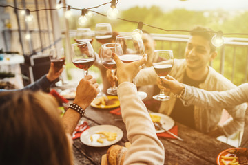 Young friends celebrating at a dinner at sunset - Detail of hands while toasting with glasses of wine - Happy people at a terrace party after the harvest before sunset - Concept of friendship