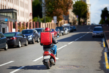 Delivery service from cafes and restaurants, delivery boy on scooter with red backpack driving fast. Courier delivering food on motorbike. Quick deliver food to customers Wall mural