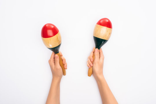 Cropped view of woman holding maracas on white background