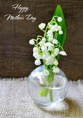Wall Murals Lily of the valley Bouquet of lilies of the valley in a glass vase on old wooden table.Lily-of-the-valley flowers.Happy Mother's Day festive concept with copy space.Selective focus.