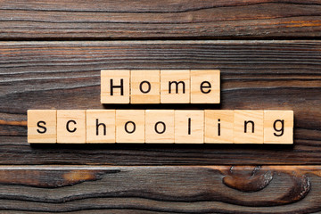 Homeschooling word written on wood block. Home schooling text on table, concept