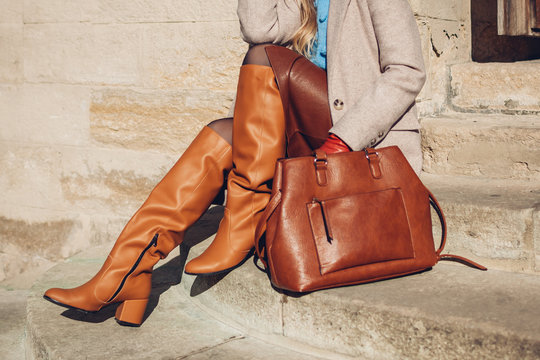 Close up of woman wearing stylish orange boots leather skirt holding purse outdoors. Spring fashion accessories clothes