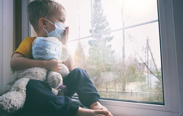 Illness child on home quarantine. Boy and his teddy bear both in protective medical masks sits on windowsill and looks out window. Virus protection, coronavirus pandemic, prevention epidemic. Wall mural