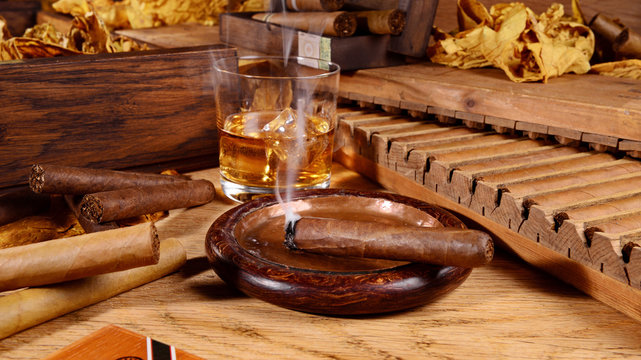 Cigars with Whisky and Tobacco Leaves on wooden Background