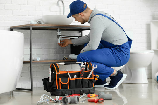 Handsome plumber repairing sink in bathroom