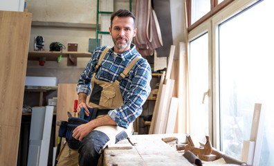 Portrait of mature carpenter posing in his carpentry workshop with tools in background Fotobehang