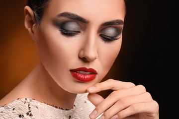 Wall Mural - Young woman with beautiful makeup on dark background