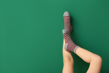 Legs of little girl in socks on color background