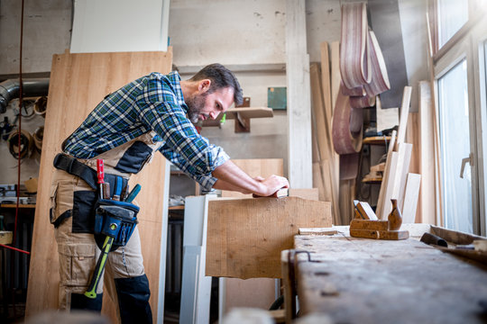 Carpenter working on woodworking in carpentry workshop