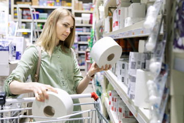 woman buy toilet paper rolls at household goods store