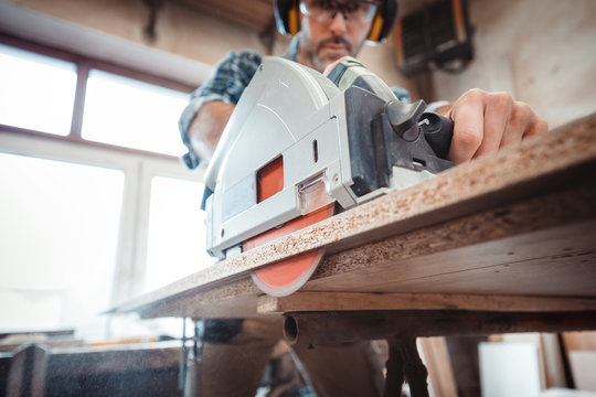 Carpenter using professional circular saw to cutting a wooden board in carpentry workshop