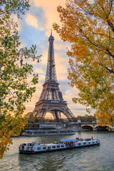 Fototapeten Paris Peniche passing in front of the Eiffel tower in Paris France on an autumn day surrounded by brown leaves of trees, tour Eiffel in the fall