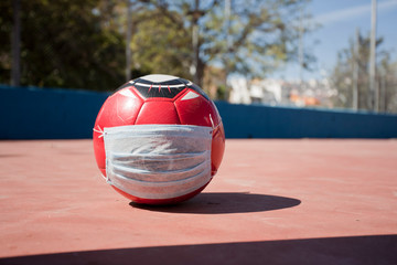 Soccer and coronavirus concept, soccer ball with respiratory mask on soccer field closed to the public, space to write