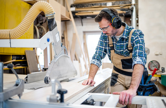 Carpenter using circular saw to cut a large wooden board at carpentry workshop